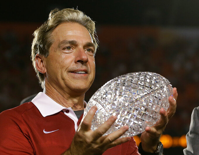 FILE - In this Jan. 7, 2013, file photo, Alabama head coach Nick Saban holds The Coaches Trophy after the BCS National Championship college football game against Notre Dame, in Miami. Alabama won 42-14. Alabama has claimed three of the decade's first six national titles while Auburn, Florida State and Ohio State have each won one. The Tide is the preseason No. 1 team again.  (AP Photo/David J. Phillip, File)
