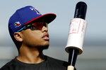 Texas Rangers' Willie Calhoun waits to bat during spring training baseball practice Friday, Feb. 14, 2020, in Surprise, Ariz. (AP Photo/Charlie Riedel)