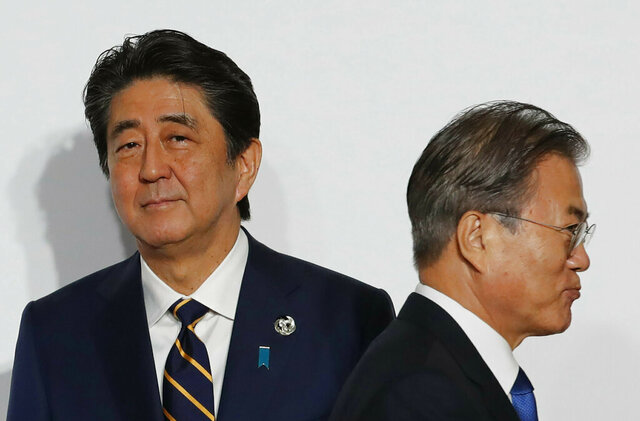 FILE - In this June 28, 2019, file photo, South Korean President Moon Jae-in, right, walks by Japanese Prime Minister Shinzo Abe upon his arrival for a welcome and family photo session at the G-20 leaders summit in Osaka, western Japan. When Abe announced his decision last month to step down as Japan's prime minster over an illness, Moon's office issued glowing praise about his unspecified contributions to bilateral ties. The rare praise came after years of intense diplomatic rows over wartime history, trade and military issues that sank the relationship between the key U.S. allies to post-war lows. (Kim Kyung-Hoon/Pool Photo via AP, File)