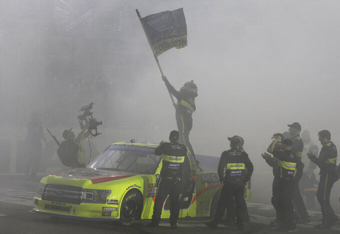 Matt Crafton, waving a flag, celebrates on the smoke-filled front stretch with his crew after winning the NASCAR Truck Series auto racing season championship Friday, Nov. 15, 2019, at Homestead-Miami Speedway in Homestead, Fla. (AP Photo/Terry Renna)