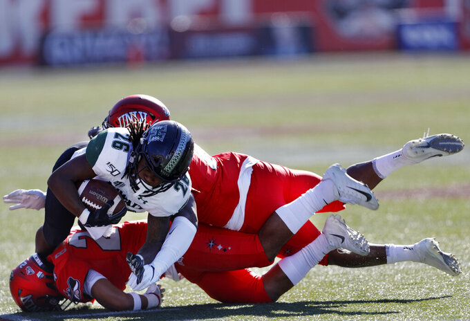 Hawaii running back Miles Reed (26) is tackled by UNLV defensive back Tykenzie Daniels, top, and defensive back Bryce Jackson (24) during the first half of an NCAA college football game in Las Vegas, Saturday, Nov. 16, 2019. (Steve Marcus/Las Vegas Sun via AP)