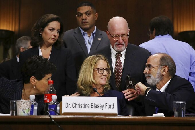 FILE - In this Thursday, Sept. 27, 2018, file photo, Christine Blasey Ford and her attorneys Debra Katz, foreground left, and Michael Bromwich, foreground right, take a break during testimony before the Senate Judiciary Committee in Washington. Trump nominee Brett Kavanaugh was narrowly confirmed to fill a vacancy on the U.S. Supreme Court after explosive Senate hearings on allegations of sexual harassment and assault stemming from his high school and college years. (Win McNamee/Pool Photo via AP, File)