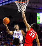 Florida guard Mike Okauru (0) attempts to score as Georgia forward Nicolas Claxton (33) blocks him during an NCAA college basketball game Saturday, March 2, 2019, in Gainesville, Fla. (Lauren Bacho/The Gainesville Sun via AP)