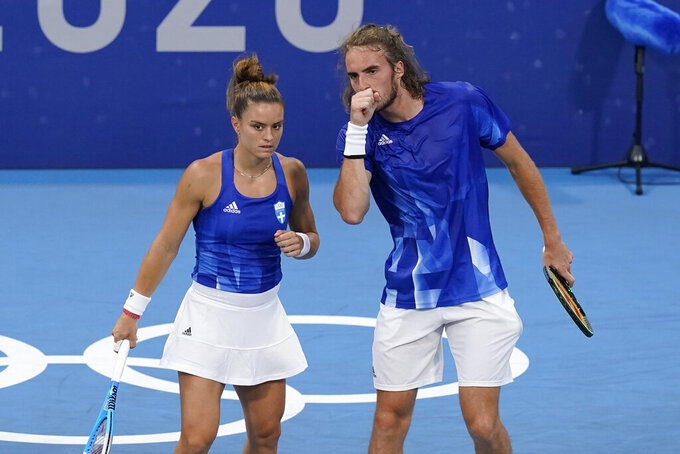 Maria Sakkari, left, and Stefanos Tsitsipas, of Greece, speak during a first round mixed doubles tennis match against Gabriela Dabrowski and Felix Auger-Aliassime, of Canada, at the 2020 Summer Olympics, Wednesday, July 28, 2021, in Tokyo, Japan. (AP Photo/Patrick Semansky)
