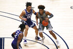 West Virginia guard Miles McBride (4) is defended by Kansas State guards Mike McGuirl (0) and Selton Miguel (2) during the first half of an NCAA college basketball game Saturday, Feb. 27, 2021, in Morgantown, W.Va. (AP Photo/Kathleen Batten)