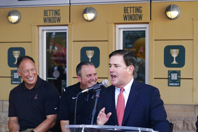 Arizona Republican Gov. Doug Ducey, right, speaks at a news conference as the Arizona Diamondbacks partner with Caesars Entertainment setting up temporary betting windows at the Diamondbacks' Chase Field, the baseball home of the Diamondbacks baseball team, as Diamondbacks front office members Luis Gonzalez, left, president and CEO Derrick Hall laugh in the background Thursday, Sept. 9, 2021, in Phoenix. The on-site sports betting permanent home just outside Chase Field will be opened in the coming months. (AP Photo/Ross D. Franklin)