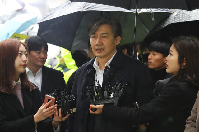 Former Justice Minister Cho Kuk, center, speaks upon his arrival at the Seoul Eastern District Court in Seoul, South Korea, Thursday, Dec. 26, 2019. Cho on Thursday attended a court hearing that will decide on the issuance of an arrest warrant for him over his suspected role in ending an inspection into bribery allegations involving a former Busan vice mayor, Yonhap news agency reported. (AP Photo/Ahn Young-joon)