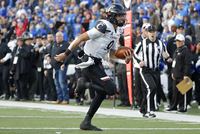 Cincinnati quarterback Desmond Ridder runs for a touchdown against Memphis during the first half of an NCAA college football game for the American Athletic Conference championship Saturday, Dec. 7, 2019, in Memphis, Tenn. Cincinnati's Desmond Ridder is known for his dual-threat skills. JT Daniels has used his arm strength to add balance to Georgia's attack.The two quarterbacks also boast impressive football intelligence, and that may be the biggest reason neither has lost a game as a starter this season as they prepare to meet in Friday's Peach Bowl.(AP Photo/Mark Humphrey)