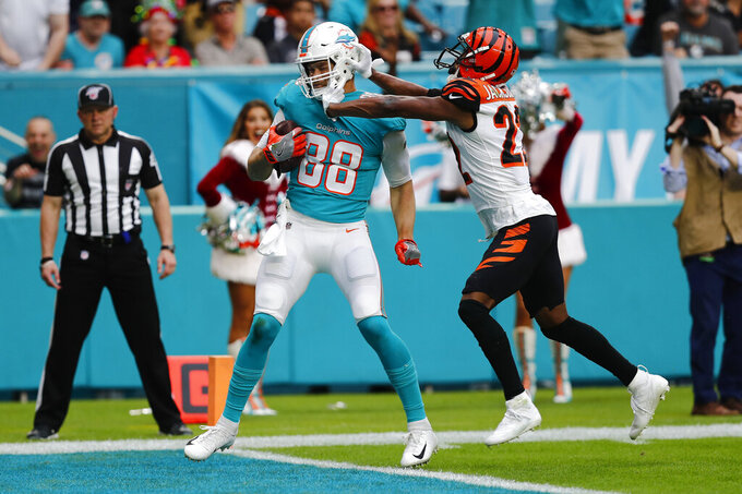 Cincinnati Bengals cornerback William Jackson (22) pushes Miami Dolphins tight end Mike Gesicki (88) as Gesicki scores a touchdown, during the first half at an NFL football game, Sunday, Dec. 22, 2019, in Miami Gardens, Fla. (AP Photo/Brynn Anderson)