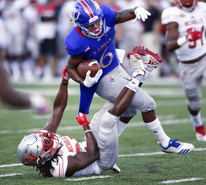 Nicholls State defensive back Jonavon Lewis (27) pulls down Kansas wide receiver Quan Hampton (6) during the first quarter of an NCAA college football game in Lawrence, Kan., Saturday, Sept. 1, 2018. (AP Photo/Reed Hoffmann)