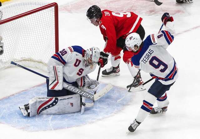 Canada's Connor Zary (9) is stopped by U.S. goalie Spencer Knight (30) as Trevor Zegras (9) defends during the second period of the championship game in the IIHF World Junior Hockey Championship, Tuesday, Jan. 5, 2021, in Edmonton, Alberta. (Jason Franson/The Canadian Press via AP)