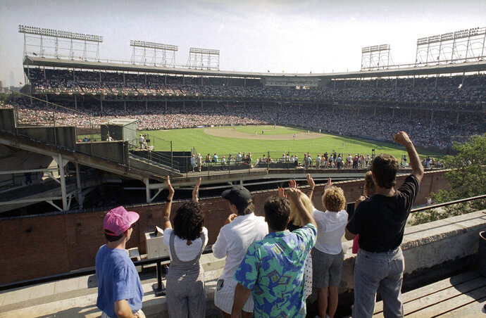 FILE - In this Monday, July 9, 1990, file photo, spectators watch an All-Star Game practice session from the roof of a building just outside Chicago's Wrigley Field. This week, Major League Baseball players and owners reached an agreement to play an abbreviated, 60-game season that would start July 23 or 24 in teams' home ballparks. But the seats will be empty. Instead, fans hoping to see a game in person will be have to settle for pressing their faces up against hotel windows, squinting through metal grates or climb to rooftops when baseball returns this month in otherwise empty stadiums. (AP Photo/Seth Perlman, File)