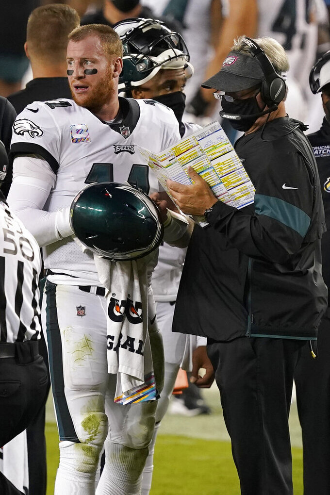 Philadelphia Eagles quarterback Carson Wentz (11) talks with head coach Doug Pederson during the second half of an NFL football game against the San Francisco 49ers in Santa Clara, Calif., Sunday, Oct. 4, 2020. (AP Photo/Tony Avelar)