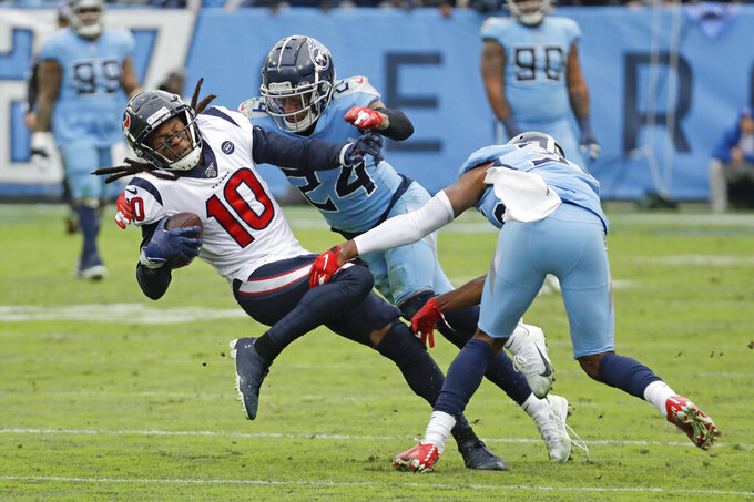 Houston Texans wide receiver DeAndre Hopkins (10) is stopped by Tennessee Titans strong safety Kenny Vaccaro (24) in the second half of an NFL football game Sunday, Dec. 15, 2019, in Nashville, Tenn. (AP Photo/James Kenney)