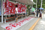 """An anti-coup protester uses red paint as he writes slogans at a bus stop on Wednesday April 14, 2021 in Yangon, Myanmar. Anti-coup protesters kept public demonstrations going despite the threat of lethal violence from security forces. The words reads """"We do not accept military coup"""". (AP Photo)"""