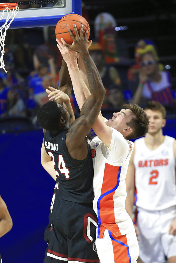 South Carolina forward Keyshawn Bryant (24) and Florida forward Colin Castleton (12) reach for a rebound during the second half of an NCAA college basketball game Wednesday, Feb. 3, 2021, in Gainesville, Fla. (AP Photo/Matt Stamey)