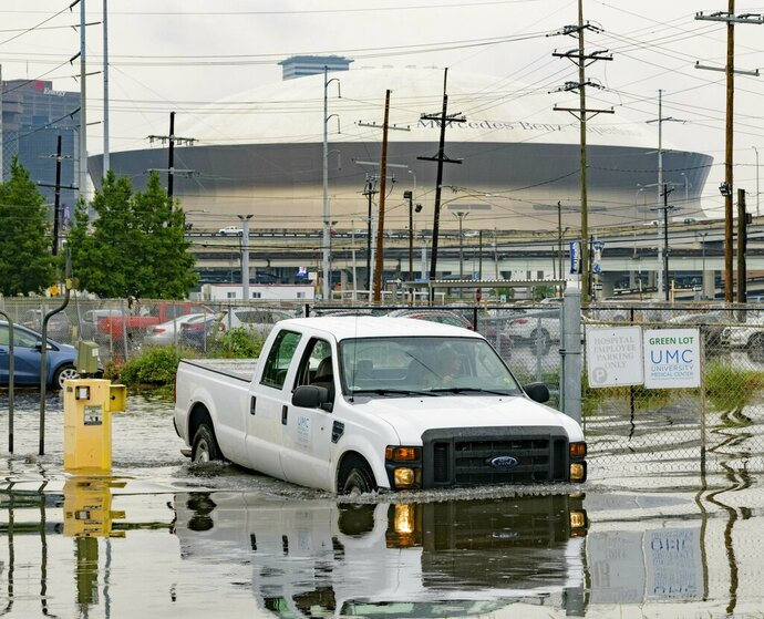Frank Conforto Jr. drives a University Medical Center (UMC) truck with the Mercedes-Benz Superdome in the background on Glavez Street in New Orleans after flooding from a storm Wednesday, July 10, 2019. Louisiana Gov. John Bel Edwards has declared a state of emergency in anticipation of tropical weather that could dump as much as 15 inches (38 centimeters) of rain in the state over the coming days. (AP Photo/Matthew Hinton)