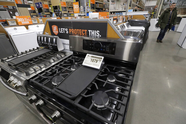 In this Monday, Jan. 27, 2020 photo a passer-by walks near stoves, front, at a Home Depot store location, in Boston. On Tuesday, Jan. 28, the Conference Board reports on U.S. consumer confidence for January.  (AP Photo/Steven Senne)