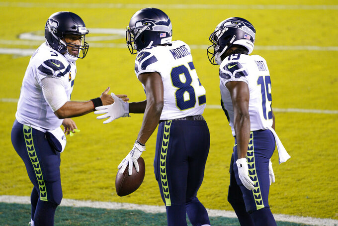 Seattle Seahawks' David Moore (83) celebrates with Russell Wilson (3) and Penny Hart (19) after scoring a touchdown during the first half of an NFL football game against the Philadelphia Eagles, Monday, Nov. 30, 2020, in Philadelphia. (AP Photo/Chris Szagola)