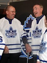 FILE - In this March 22, 2005, file photo, Toronto Marlies alumni Mike Pelyk, left, and Bob Nevin laugh after the new name and logo for the Toronto Maple Leafs AHL affiliate was unveiled in Toronto. Nevin, a fan favorite who won two Stanley Cups with the Maple Leafs before a successful run as captain of the New York Rangers, has died. He was 82. The NHL said he died early Monday, Sept. 21, 2020, but did not give a cause. (Frank Gunn/The Canadian Press via AP, File)