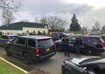 Police officers work the scene where a suspect was shot at a Cascade Middle School in Eugene, Ore, on Friday, Jan. 11, 2019. Eugene police Lt. Jennifer Bills told reporters that the incident began with a dispute outside the school. It wasn't clear who was involved and no further details were released. (Chris Pietsch/The Register-Guard via AP)
