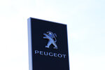 The logo of French car maker maker Peugeot is seen outside a technical center Tuesday, May 26, 2020 in Villacoublay, west of Paris. French President Emmanuel Macron is set to unveil on Tuesday new measures to rescue the country's car industry, which has been hammered by the virus lockdown and the resulting recession. The issue is politically sensitive, since France is proud of its auto industry, which employs 400,000 people in the country and is a big part of its manufacturing sector. (AP Photo/Michel Euler)