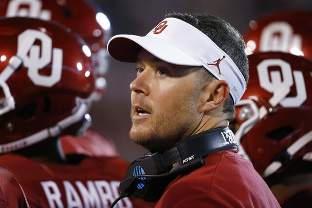 FILE - In this Saturday, Nov. 9, 2019 file photo, Oklahoma head coach Lincoln Riley talks with players during an NCAA college football game between Iowa State and Oklahoma in Norman, Okla. As usual, Riley is taking his time naming a starting quarterback. (AP Photo/Sue Ogrocki, File)