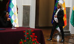 Bolivia's interim President Jeanine Anez, right, walks towards President of the Senate Monica Eva Copa to enact a law to hold new elections in La Paz, Bolivia, Sunday, Nov. 24, 2019. Bolivia is struggling to stabilize after weeks of anti-government protests and violence in which at least 30 people have been killed. Former president Evo Morales resigned on Nov. 10 after an election that the opposition said was rigged. (AP Photo/Juan Karita)