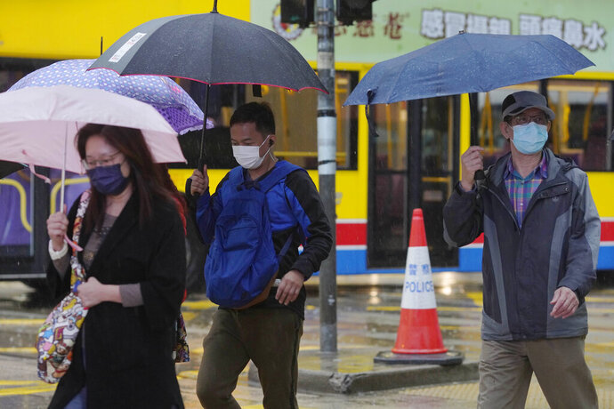 People wear protective face masks on a street corner in rain in Hong Kong, Thursday, Feb. 13, 2020. COVID-19 viral illness has sickened tens of thousands of people in China since December. (AP Photo/Vincent Yu)