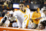FILE - In this Nov. 24, 2018, file photo, Tennessee quarterback Jarrett Guarantano bumps fists with teammates on the sideline during the second half of an NCAA college football game against Vanderbilt in Nashville, Tenn. Guarantano is working with his fourth offensive coordinator and fourth quarterback coach in as many seasons, but he believes he's got a winning combination this time. (AP Photo/Mark Humphrey, File)