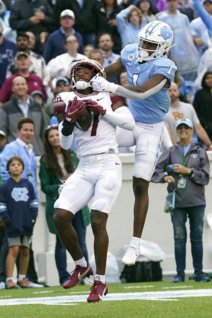 Florida State defensive back Jarrian Jones (7) intercepts a pass while North Carolina wide receiver Khafre Brown (1) reaches for the ball during the first half of an NCAA college football game in Chapel Hill, N.C., Saturday, Oct. 9, 2021. (AP Photo/Gerry Broome)