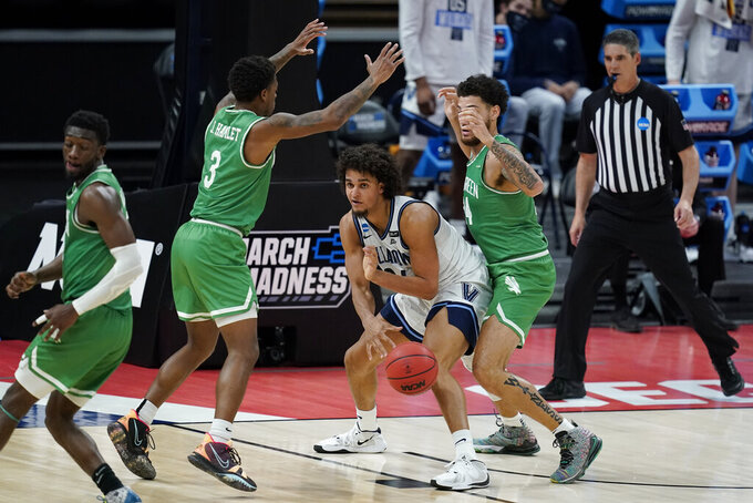 Villanova's Jeremiah Robinson-Earl (24) makes a pass against North Texas' Javion Hamlet (3) and Zachary Simmons (24) during the second half of a second-round game in the NCAA men's college basketball tournament at Bankers Life Fieldhouse, Sunday, March 21, 2021, in Indianapolis. Villanova won 84-61. (AP Photo/Darron Cummings)