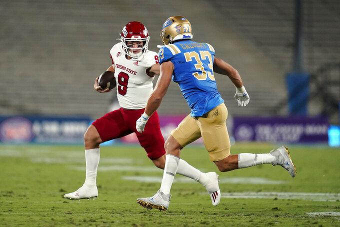 Fresno State quarterback Jake Haener (9) stiff-arms UCLA linebacker Bo Calvert (33) during the first half of an NCAA college football game Saturday, Sept. 18, 2021, in Pasadena, Calif. (AP Photo/Marcio Jose Sanchez)