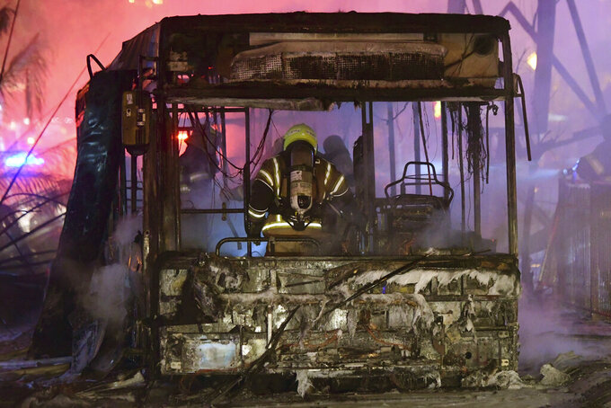 An Israeli firefighter extinguishes a burning bus after it was hit by a rocket fired from the Gaza Strip, at the central Israeli town of Holon, near Tel Aviv, Tuesday, May 11, 2021. (AP Photo/Avshalom Sassoni)