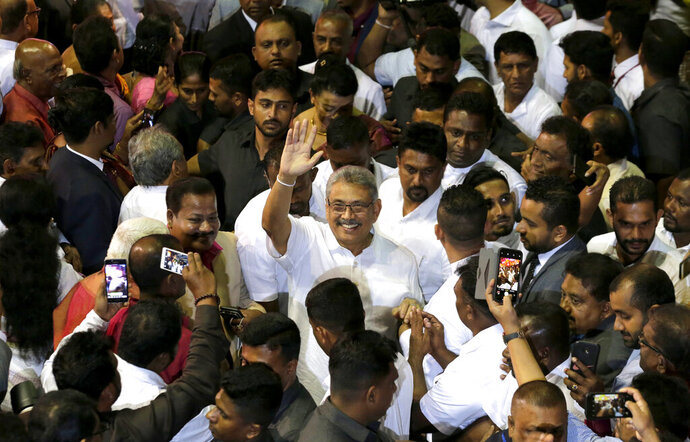 FILE - In this Aug. 11, 2019, file photo, former Sri Lankan Defense Secretary Gotabaya Rajapaksa waves to supporters during a party convention held to announce the presidential candidacy in Colombo, Sri Lanka. Gotabaya is a feared former defense official accused of human rights abuses and crushing critics, but to many Sri Lankans, he is the leader most needed after last April's Easter bomb attacks that killed more than 250 people. (AP Photo/Eranga Jayawardena, File)