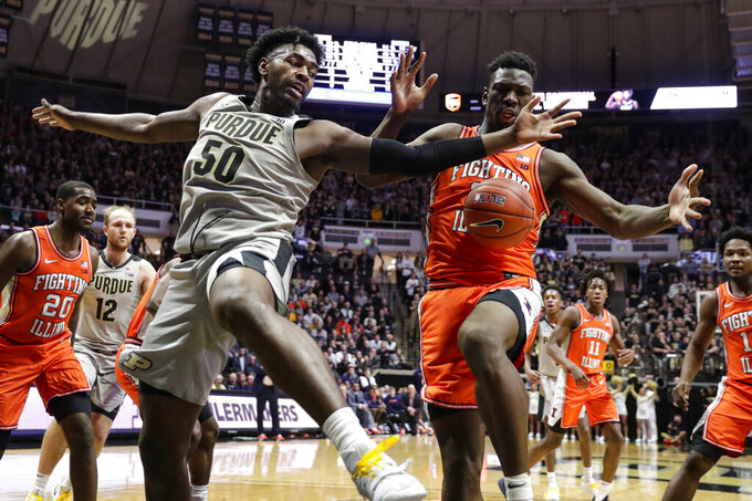 Purdue forward Trevion Williams (50) and Illinois center Kofi Cockburn (21) go for a rebound during the second half of an NCAA college basketball game in West Lafayette, Ind., Tuesday, Jan. 21, 2020. Illinois defeated Purdue 79-62. (AP Photo/Michael Conroy)