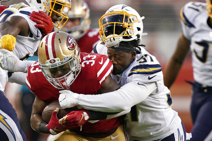 Los Angeles Chargers outside linebacker Jatavis Brown, right, loses his helmet while tackling San Francisco 49ers running back Austin Walter (33) during the first half of an NFL preseason football game in Santa Clara, Calif., Thursday, Aug. 29, 2019. (AP Photo/Tony Avelar)