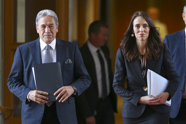 New Zealand Prime Minister Jacinda Ardern, right, walks with Deputy Prime Minister Winston Peters to the house for the budget delivery speech at Parliament in Wellington, New Zealand, Thursday, May 14, 2020. New Zealand's government plans to borrow and spend vast amounts of money as it tries to keep unemployment below 10% in the wake of the coronavirus pandemic. (Hagen Hopkins/Pool Photo via AP)