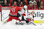 New Jersey Devils goalie Cory Schneider defends the goal while Devils' Steven Santini (16) defends against Carolina Hurricanes Andrei Svechnikov (37), of Russia, during the first period of an NHL hockey game in Raleigh, N.C., Thursday, April 4, 2019. (AP Photo/Gerry Broome)