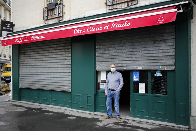 Cesar, from Portugal, stands in front of his closed bar, in Paris, Tuesday, Oct. 6, 2020. French authorities have placed the Paris region on maximum virus alert on Monday, banning festive gatherings and requiring all bars to close but allowing restaurants to remain open, as numbers of infections are rapidly increasing. (AP Photo/Francois Mori)