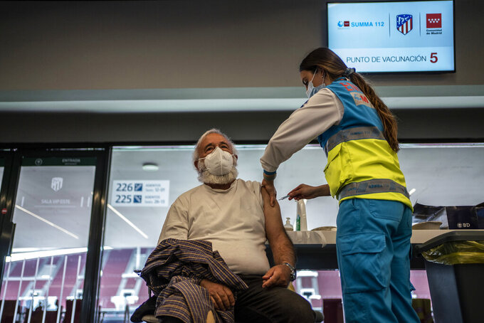 A worker from the Madrid Medical Emergency Service vaccinates a man against COVID-19 at the Wanda Metropolitano stadium, Madrid, Spain, March 30, 2021. Spain is trying to stamp out a new wave of COVID-19 among its youth thanks to a robust vaccination program that is widely supported. Spain like the rest of the European Union got off to a slow start to compared to the United States and Britain when the first vaccines were released. But it has quickly made up ground once deliveries by drug makers started flowing. (AP Photo/Olmo Calvo)