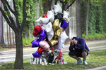 FILE - In this Sept 9, 2019, file photo, Shawn Price mourns at a memorial in Richfield, Minn. near where police shot and killed Brian J. Quinones who had streamed himself live on Facebook during a police chase after he apparently emerged from his car holding a knife and refused their commands to drop it Saturday night. The Hennepin County Attorney's Office will not file criminal charges against Richfield or Edina police officers for the fatal shooting of Quinones-Rosario, Hennepin County Attorney Mike Freeman announced Monday, Feb. 10, 2020. (AP Photo/Jim Mone, File)