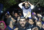 Ziad Itani, a Lebanese stage actor, who was indicted on charges of collaborating with Israel and drug possession, is carried by his neighbors and relatives after he was released by Lebanese authorities, at his house, in Beirut, Lebanon, Tuesday, March 13, 2018. Itani was released on Tuesday and cleared of charges, while the officer who built the case against him was ordered detained. (AP Photo/Hussein Malla)