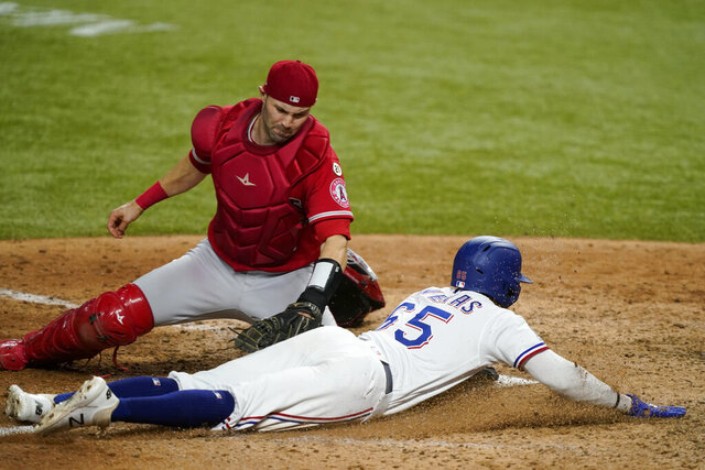 Los Angeles Angels catcher Anthony Bemboom is unable to get the tag on Texas Rangers' Leody Taveras (65), who stole home during the sixth inning of a baseball game in Arlington, Texas, Wednesday, Sept. 9, 2020. (AP Photo/Tony Gutierrez)