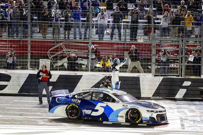 Kyle Larson climbs out of his car at the finish line as he celebrates winning the NASCAR Cup Series auto race at Charlotte Motor Speedway in Concord, N.C., late Sunday, May 30, 2021. (AP Photo/Nell Redmond)