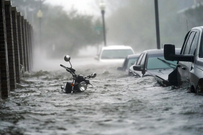 Cars and a motorcycle are underwater as water floods a street, Wednesday, Sept. 16, 2020, in Pensacola, Fla. Hurricane Sally made landfall Wednesday near Gulf Shores, Alabama, as a Category 2 storm, pushing a surge of ocean water onto the coast and dumping torrential rain that forecasters said would cause dangerous flooding from the Florida Panhandle to Mississippi and well inland in the days ahead.(AP Photo/Gerald Herbert)