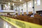 Yellow caution tape is viewed during a service at the San Gabriel Mission, Sunday, July 12, 2020, in San Gabriel, Calif. A fire on Saturday destroyed the rooftop and most of the interior of the nearly 250-year-old California church that was undergoing renovation. (AP Photo/Marcio Jose Sanchez)