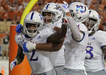 Kansas' Daylon Charlot (2) celebrates with teammates after catching a 2-point conversion during the second half of the team's NCAA college football game against Texas in Austin, Texas, Saturday, Oct. 19, 2019. (AP Photo/Chuck Burton)