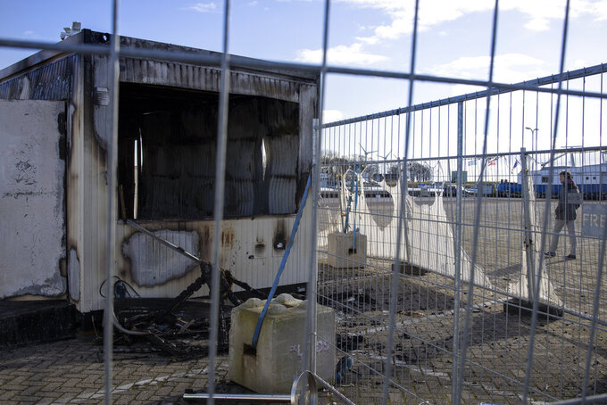 FILE - In this Jan. 24, 2021, file photo, a person walks past a burned-out coronavirus testing facility in the fishing village of Urk in the Netherlands after it was set on fire the night before by rioting youths protesting on the first night of a nationwide curfew. A Dutch court on Tuesday July 20, 2021, has convicted two men of arson for torching a coronavirus test location in a fishing village during violent protests that followed the introduction of a nationwide lockdown curfew. (AP Photo/Peter Dejong, File)