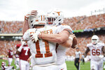 Texas quarterback Sam Ehlinger (11) celebrates after scrambling for a 9-yard touchdown against Oklahoma with teammate Andrew Beck (47) during the first half of an NCAA college football game at the Cotton Bowl, Saturday, Oct. 6, 2018, in Dallas. (AP Photo/Cooper Neill)